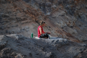 Man meditating on a cliff at Kauai's Waimea Canyon.