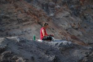 Man meditating on a cliff at Kauai's Waimea Canyon.